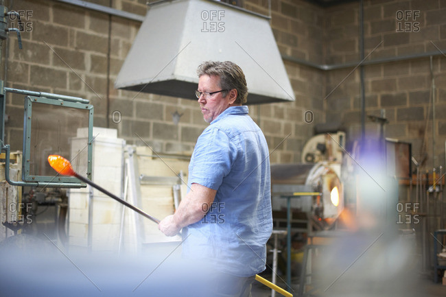 Glassblowers in workshop holding blowpipe