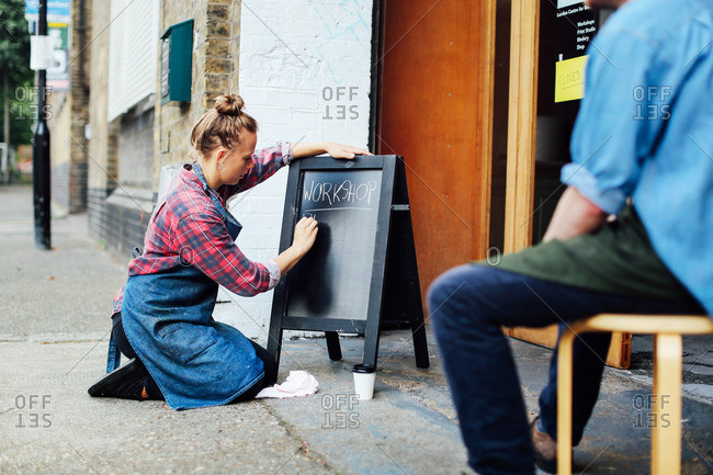 Young woman kneeling on pavement and writing on blackboard outside workshop