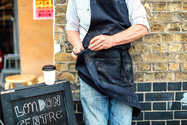 Senior craftsman outside workshop, cleaning glasses with his apron, mid section