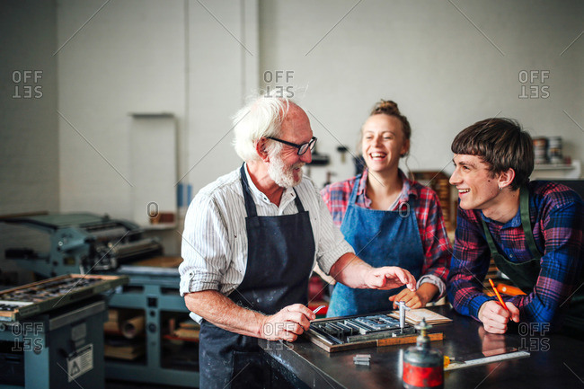 Senior craftsman laughing with young craftsman and craftswoman in letterpress workshop