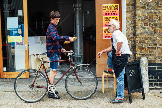 Young man with pushbike looking at post and standing with senior craftsman outside print workshop