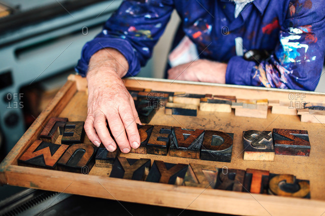 Senior craftsman reaching for wooden letterpress letters, mid section