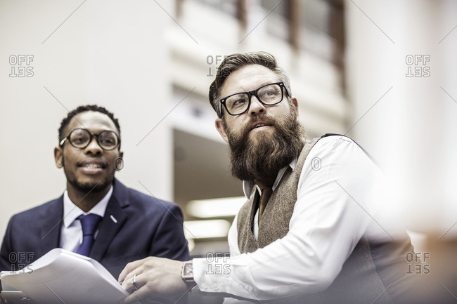 Two businessmen with paperwork, watching in office