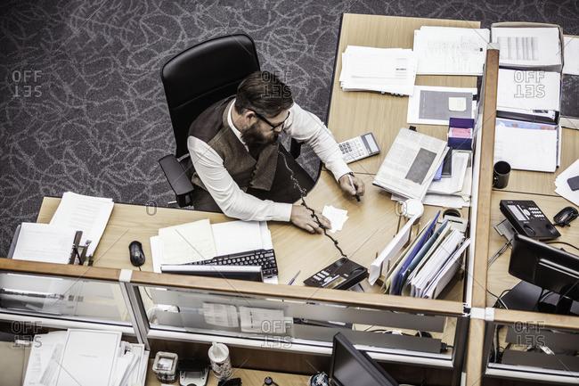 Overhead view of businessman talking on landline at office desk