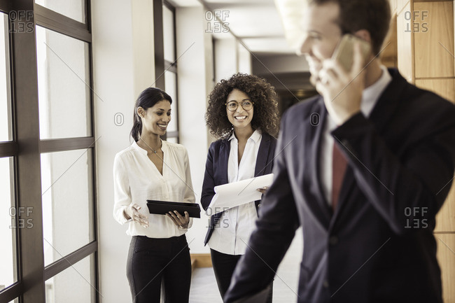 Young businesswomen and businessman in office corridor