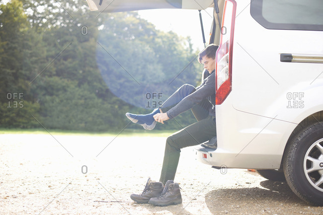 Man sitting in automobile boot putting on socks