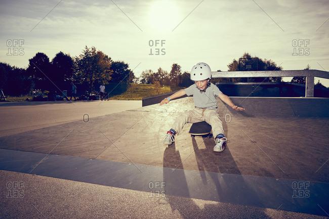 Boy sitting on skateboard in park