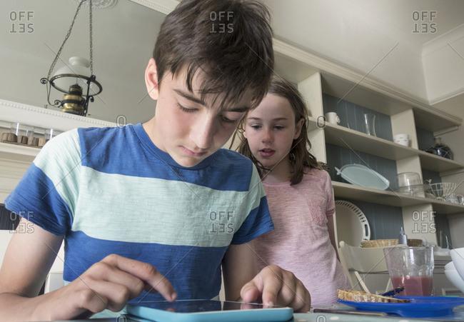Girl and boy using digital tablet