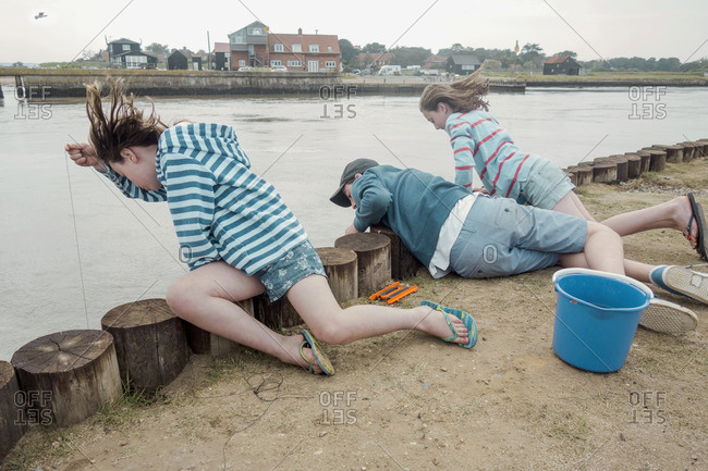 Children looking over side of pier into water, Southwold, Suffolk, UK