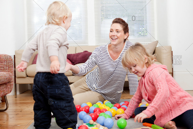 Mother and children playing with plastic balls