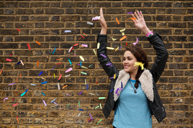 Young woman dropping colorful confetti against brick wall
