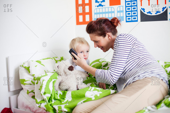 Mother holding cell phone to sons ear in bed