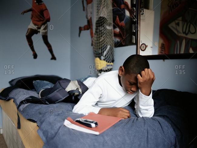 Worried boy lying on bed