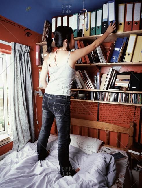 Teenage girl standing on bed