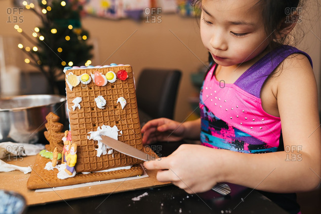 Girl frosting a gingerbread house