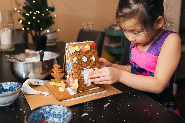 Girl assembling a gingerbread house