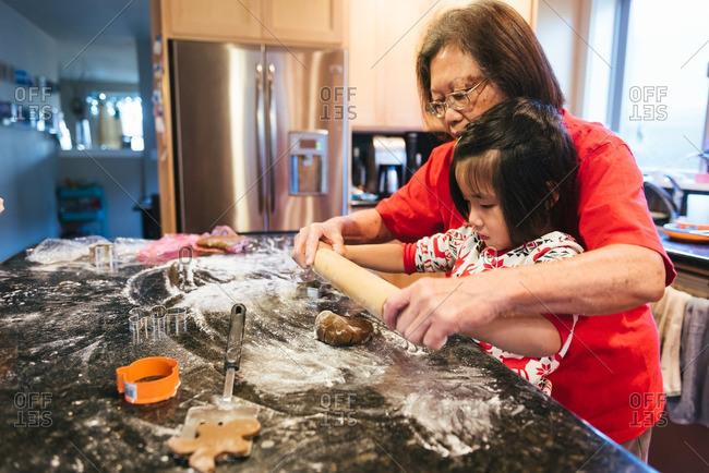 Woman helping girl make Christmas cookies