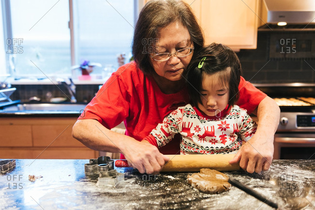 Woman helping girl bake Christmas cookies