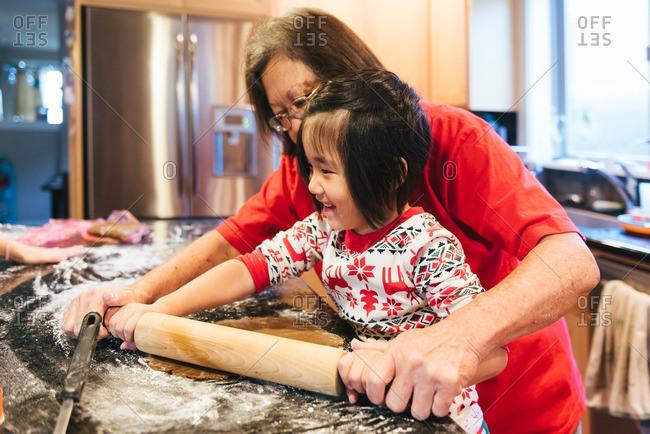 Woman and smiling girl baking Christmas cookies