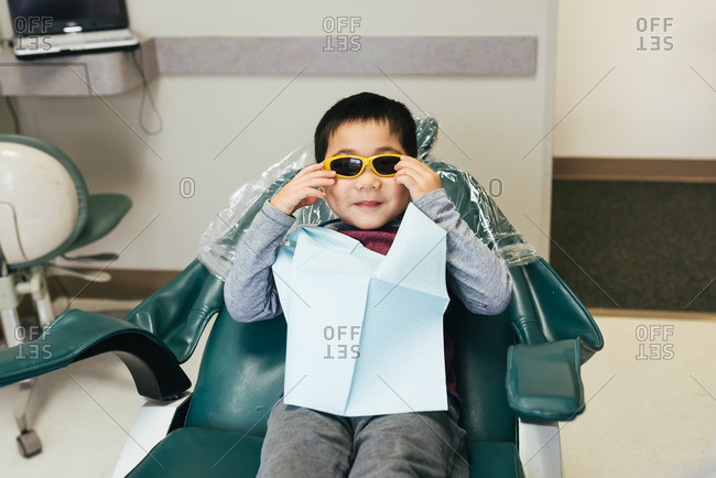 Boy in dentist chair wearing sunglasses