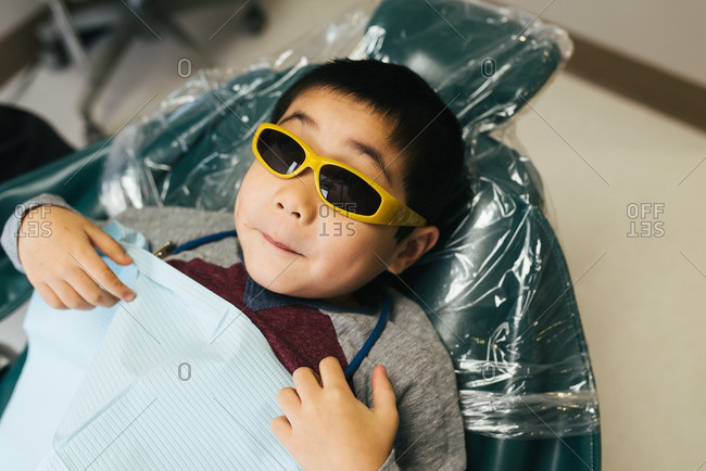 Boy in dentist chair with sunglasses