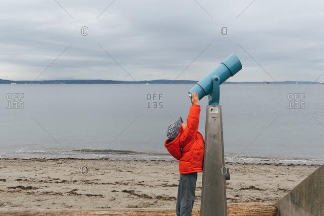 Boy by telescope in Seattle