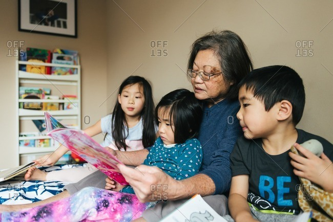 Woman reading with three kids