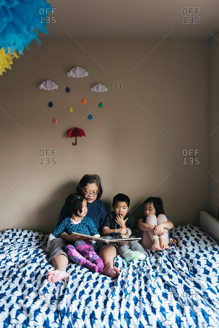 Woman reading with kids on bed