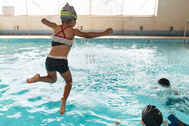 Girl jumping into indoor pool