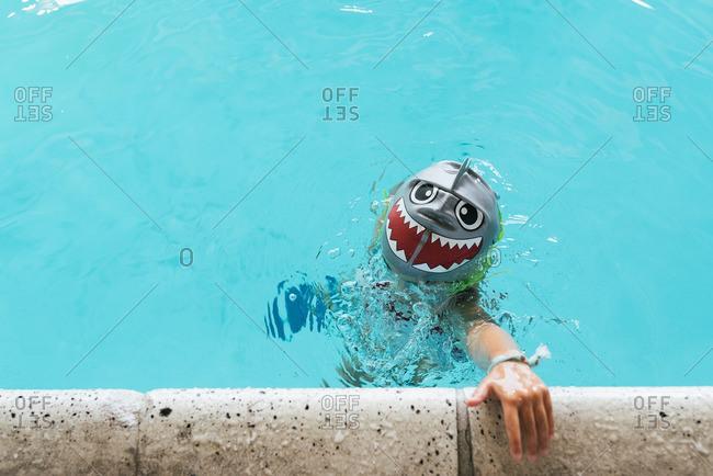 Child in pool with shark swim cap
