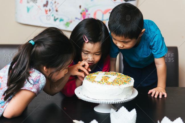Three kids around a birthday cake