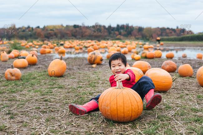Smiling boy playing on pumpkin