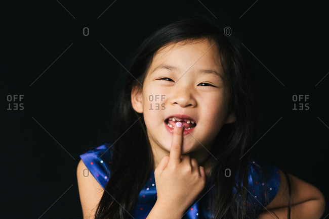 Asian girl showing growing tooth