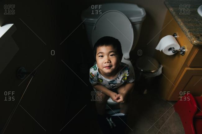 Boy sitting on the toilet