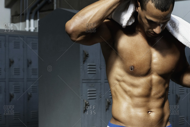 Bare chested mixed race man in locker room