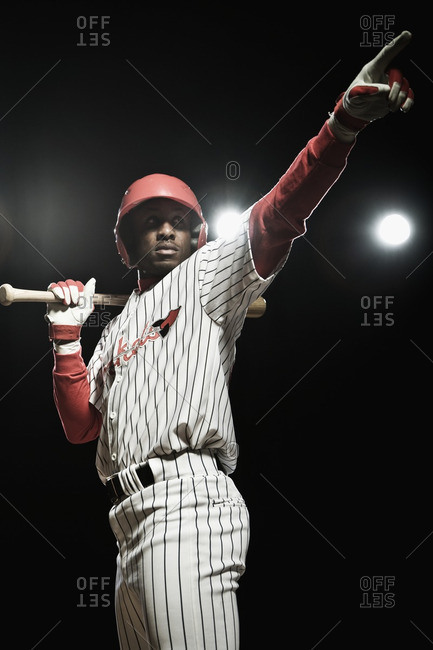 African baseball player holding bat and pointing