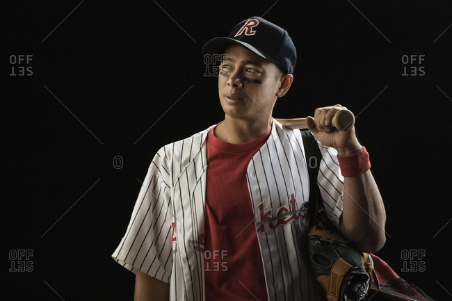 Mixed race baseball player holding bat
