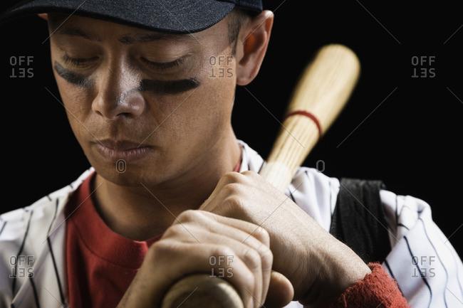 Mixed race baseball player holding bat
