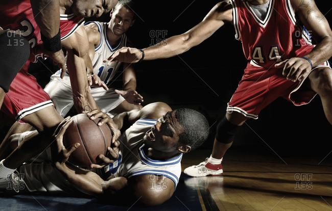 Multi-ethnic basketball players struggling for basketball