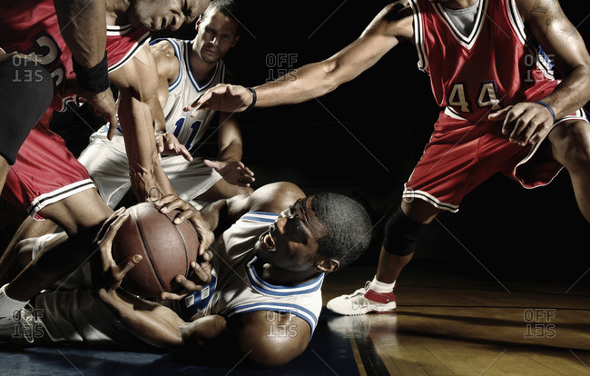 Multi-ethnic basketball players struggling for basketball