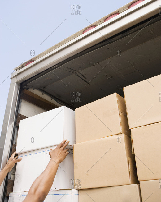 Hands reaching for boxes in back of truck
