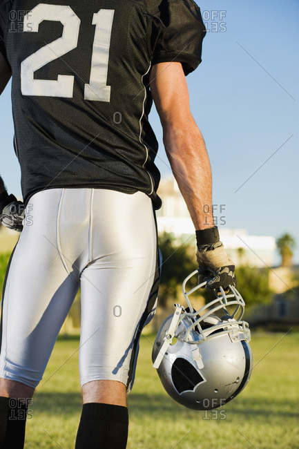 Rear view of football player holding helmet