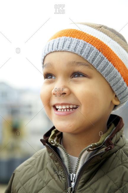 Mixed race boy in cap outdoors
