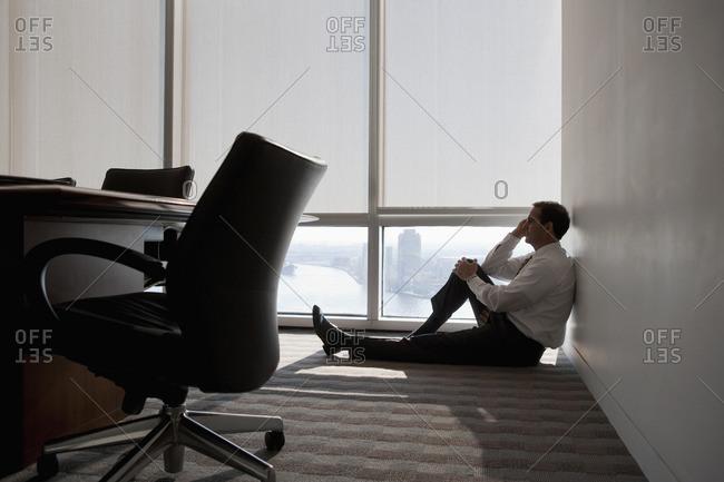 Mixed race businessman sitting on office floor next to window