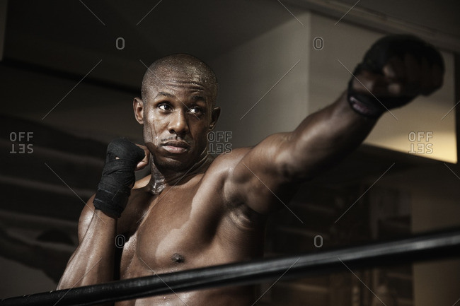 African boxer punching in boxing ring