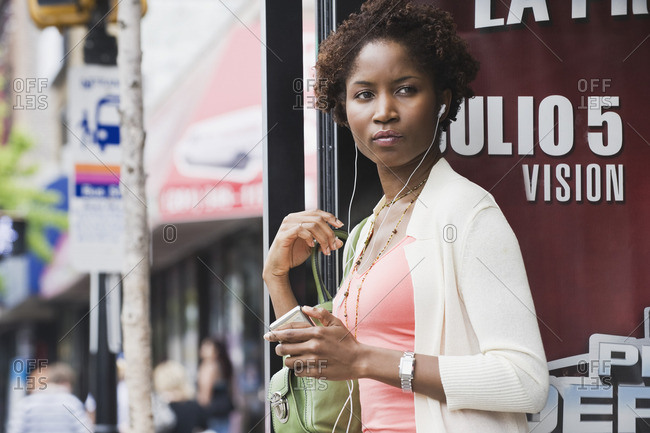 African woman listening to mp3 player at bus stop