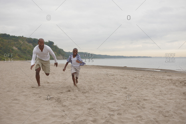 Black father and son running on beach