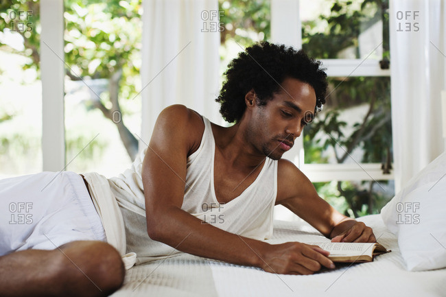 Mixed race man laying on bed reading