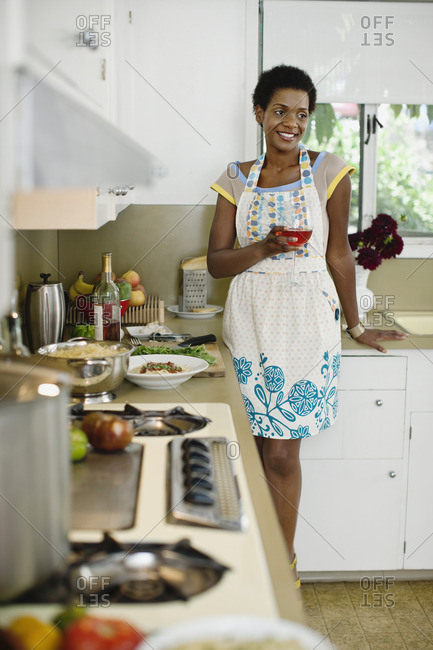African American woman drinking wine and cooking