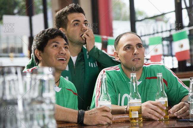 Hispanic men watching television in sports bar